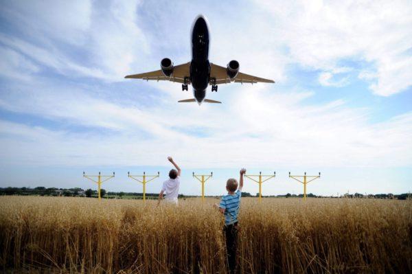 Heathrow Airport kids waving in field